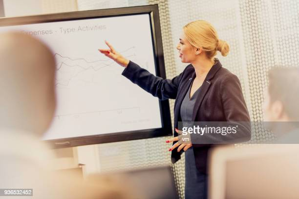 female analyst explaining graph - financial analyst stock photos and pictures