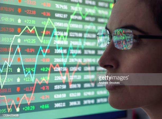 female analyst viewing financial market data on a screen. - börsenhändler stock-fotos und bilder