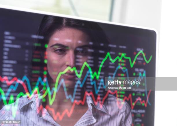 female analyst viewing financial market data on a screen. - stock trader stock pictures, royalty-free photos & images