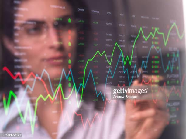 female analyst viewing financial market data on a screen. - finanzberuf stock-fotos und bilder