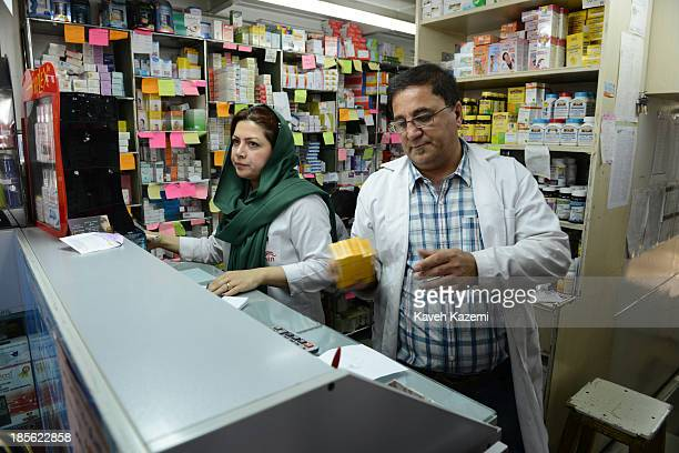 Female and a male pharmacists attend to people in a pharmacy on October 13, 2013 in Tehran, Iran. People in Iran have suffered severely due to the...