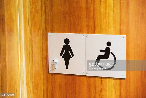 Female and disabled signs on door of office toilets, close-up