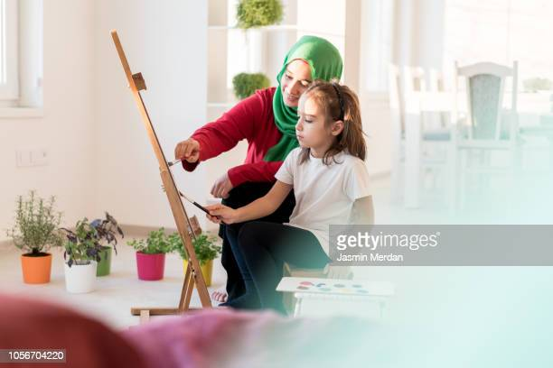 female and little kid painting at home - kunst kultur und unterhaltung fotos stock-fotos und bilder