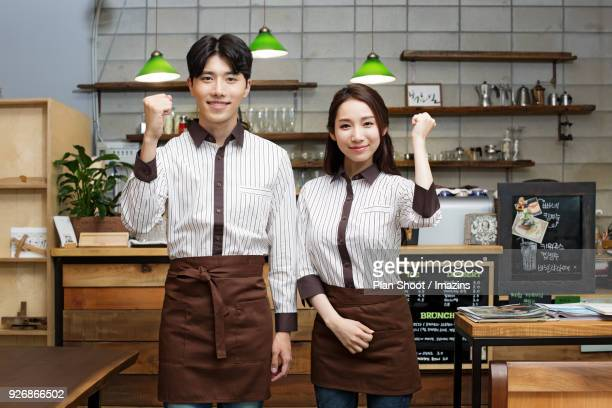 Female and male baristas at a cafe
