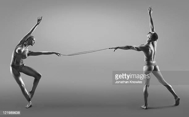 Female and male dancers connected through liquid