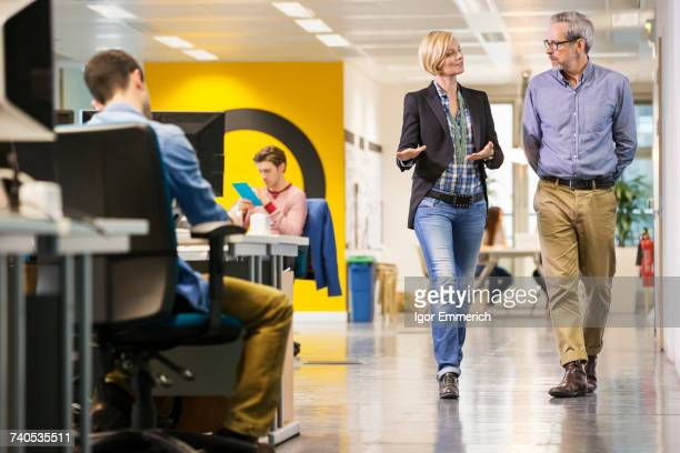 Female and male digital designers walking and talking in office