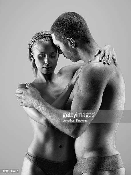 Female and male embraced in paint
