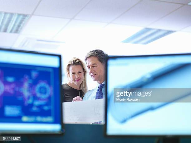 Female and male engineer designers discussing plans in office