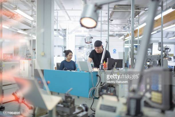 female and male engineers working at lathes in engineering factory. - monty rakusen stock pictures, royalty-free photos & images