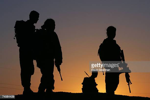 Female and male fighters from the Israeli army's Caracal battalion are silhouetted against the sunset during their evening patrol June 12 2007 along...