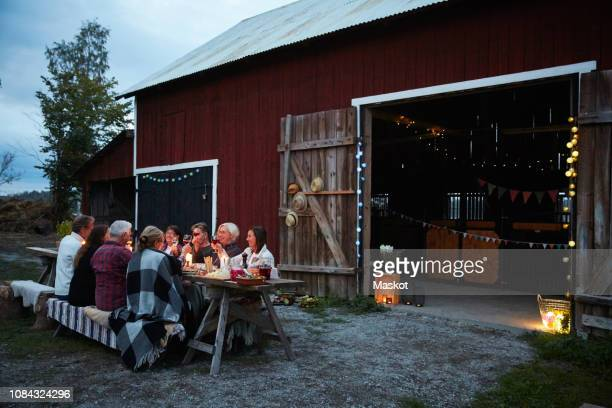 Female and male friends enjoying dinner party against barn at farm