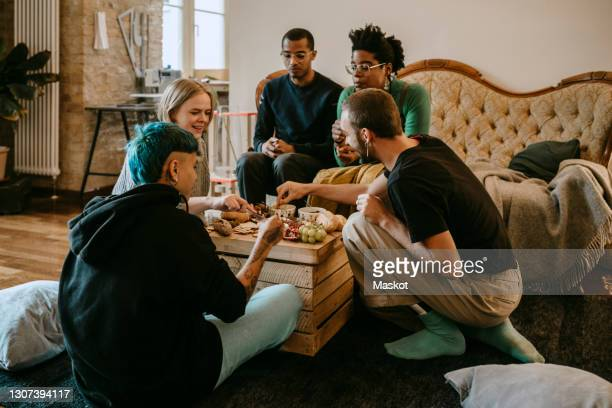 female and male friends having breakfast in living room at home - five people stock pictures, royalty-free photos & images