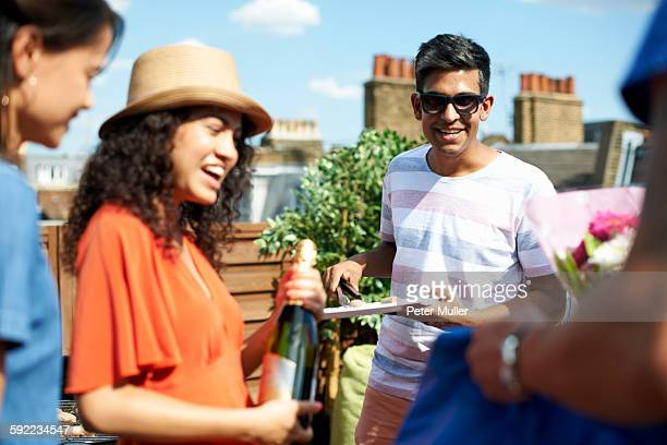 Female and male friends with champagne bottle at rooftop barbecue
