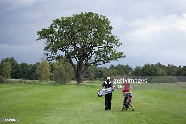 A female and male golfer walking with their golf bags, rear view