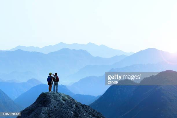 female and male hiker taking picture of sunset - horizon stock pictures, royalty-free photos & images
