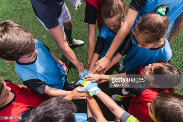 female and male kids soccer players together with hands in circle before a match - junior level stock pictures, royalty-free photos & images