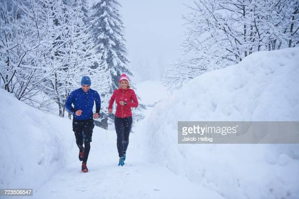 Female and male runners running in falling snow, Gstaad, Switzerland