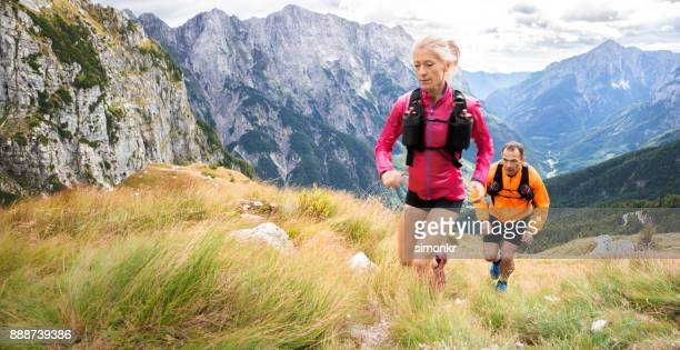 female and male runners running up hill on meadow high in mountains - cross country running stock pictures, royalty-free photos & images