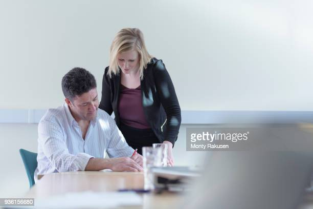 Female and male scientists signing contract about pharmaceutical project in meeting room