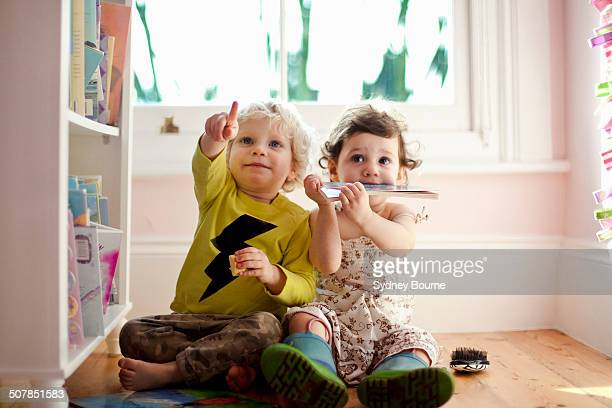 female and male toddler friends pointing and looking up - peuter stockfoto's en -beelden