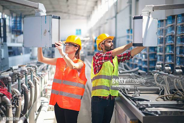 Female and male worker in factory using control panel