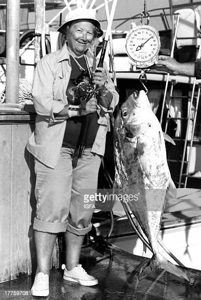 A female angler poses with her fishing rod and a 29 pound African pompano being weighed on the dock at Islamorada Florida on March 27 1981