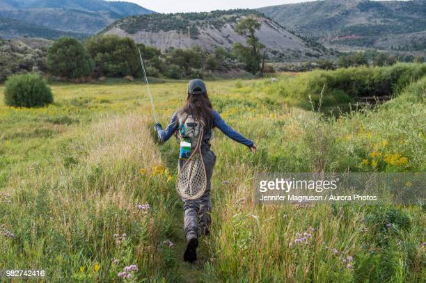 female angler walking through meadow, colorado, usa - silverthorne stock photos and pictures