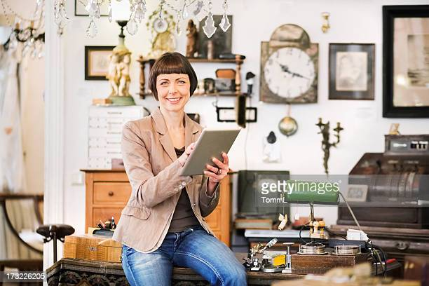 A female antique store owner using a tablet