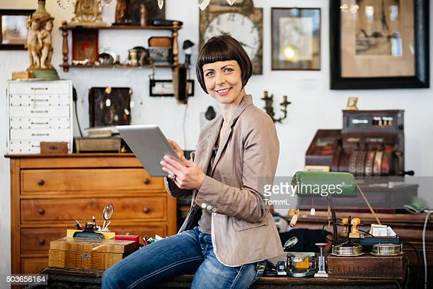 Female antique store owner using digital tablet