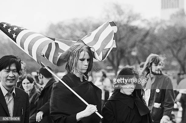 Female anti-Vietnam War protesters hold American flags and wear shrouds during a demonstration for the students killed by the National Guard at Kent...
