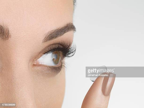 female applying contact lenses, looking away - contact lens stock pictures, royalty-free photos & images