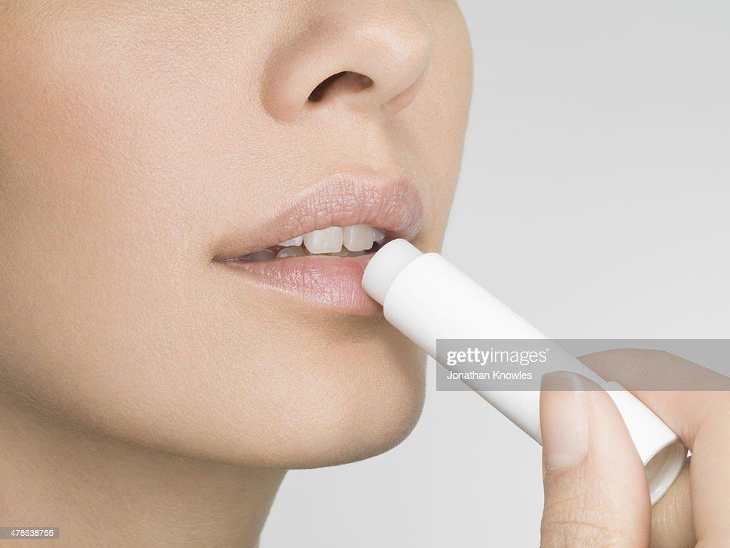 Female applying lip balm, close up, side view : Stock Photo