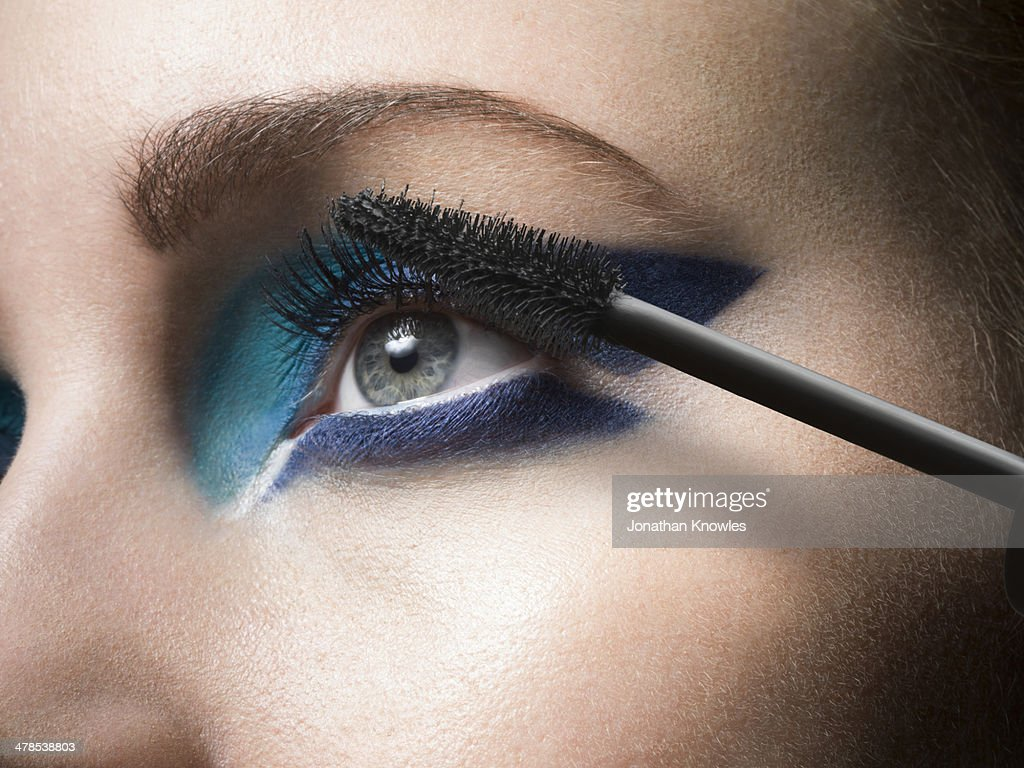 Female applying mascara, close up : Stock Photo