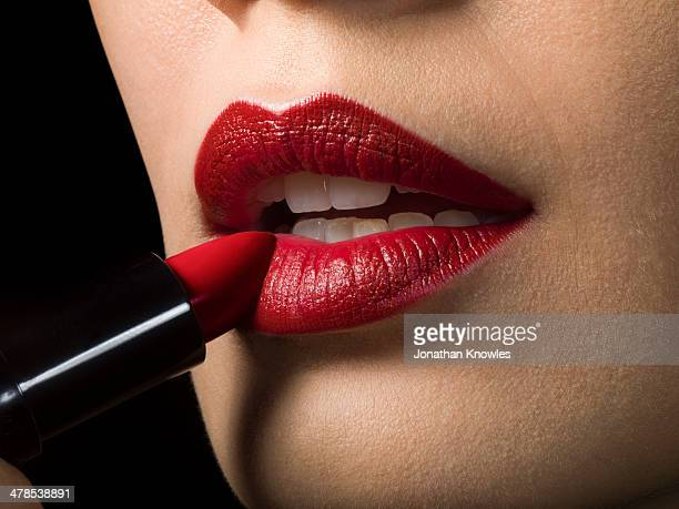 Female applying red lipstick, close up