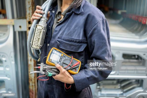 female apprentice electrician holding equipment in car factory, close up - coveralls stock pictures, royalty-free photos & images