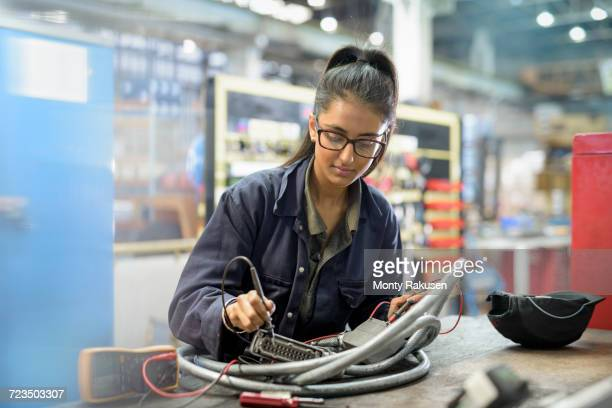 Female apprentice electrician in car factory