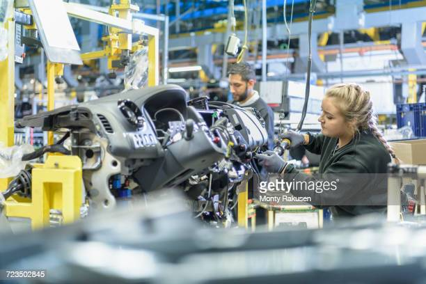 female apprentice engineer on production line in car factory - automobile industry stock pictures, royalty-free photos & images