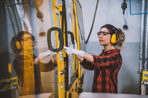 Female apprentice engineer working with CNC machine in factory - gettyimageskorea
