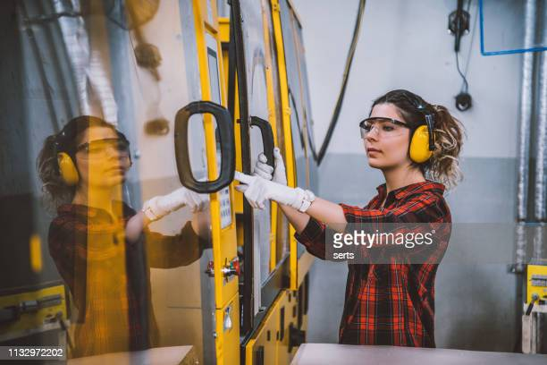 female apprentice engineer working with cnc machine in factory - trainee stock pictures, royalty-free photos & images