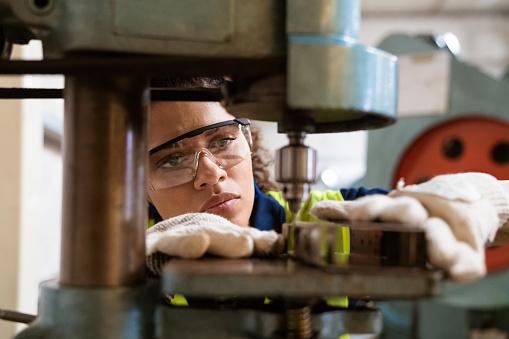 Female apprentice using yoke machine in factory 1149239358