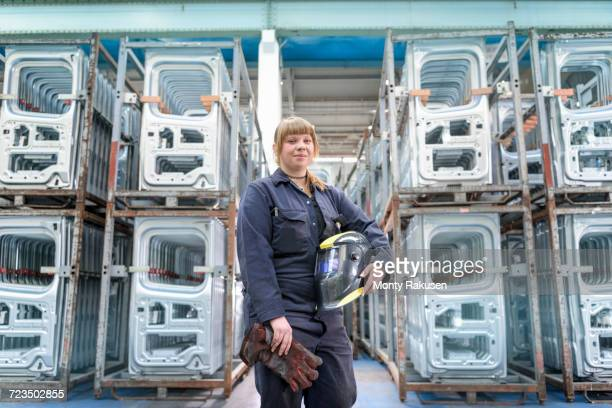 female apprentice welder holding equipment in car factory, portrait - luton stock pictures, royalty-free photos & images