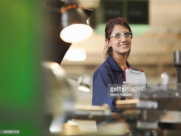 female apprentice with clipboard - schutzbrille stock-fotos und bilder
