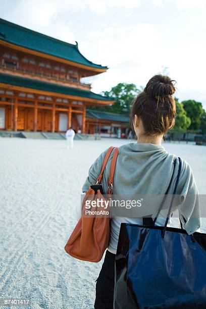 Female approaching Japanese temple, rear view