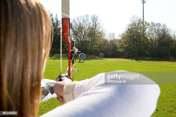 Female archer aiming arrow at target board, Munich, Bavaria, Germany