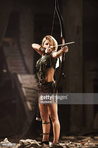 Female archer aiming with bow and arrow.