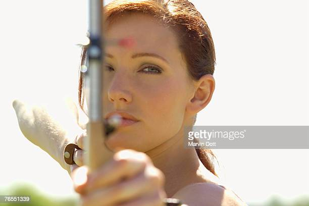 Young woman aiming with bow, focus on woman at background, close-up