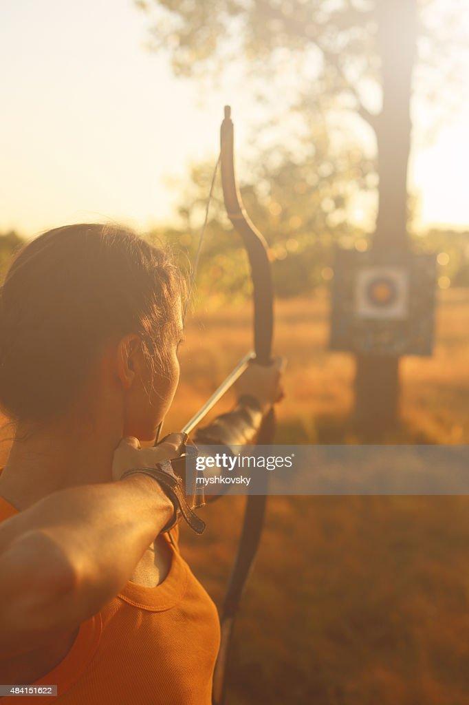 Weibliche archer im Feld bei Sonnenuntergang : Stock-Foto
