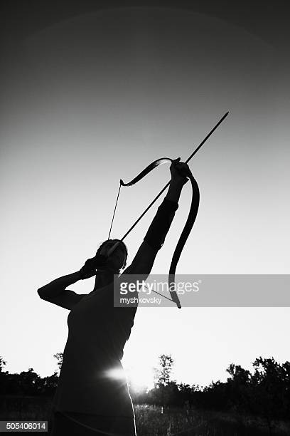 Female archer in the field at sunset