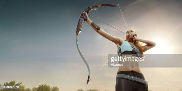 female archer shooting with the longbow at sunset - longbow stock photos and pictures