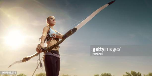 Female archer shooting with the longbow at sunset